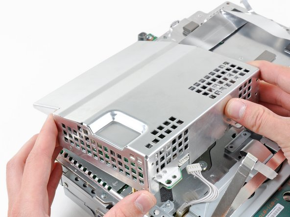 Lift the power supply by its front edge to clear the two posts attached to the motherboard.