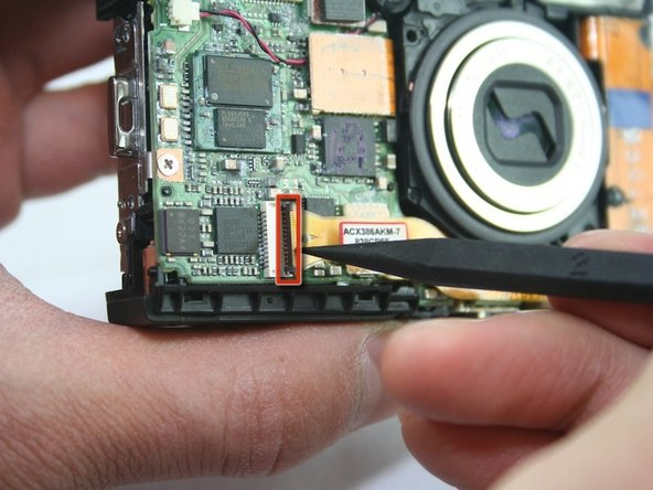 Use a spudger to lift the connector lock (black flap) at the end of the larger LCD connector ribbon on the front side of the camera.