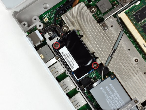 Remove the two Phillips screws at the corners of the modem.