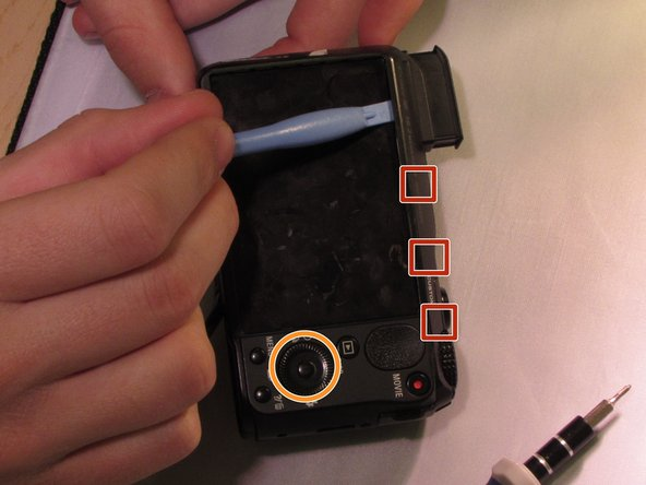 Use the plastic opening tool with a prying motion, going between the case and the LCD, from the middle of the LCD to the right of the device, undoing the claws retaining the back.