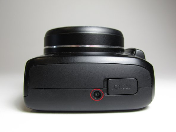 Put the camera with the lens facing up, turn it to the side where the compartment of the battery (CR1220) for time/date is located.