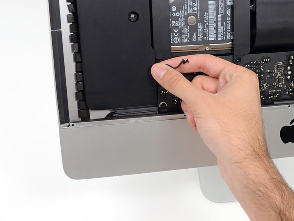 Carefully de-route the power button cable from its groove in the left speaker.
