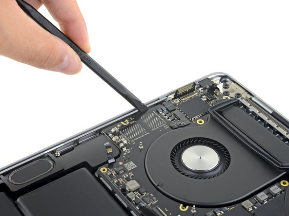 The logic board assembly is a tight fit, but you can make it easier to remove by inserting a spudger under the left edge and levering it up slightly.