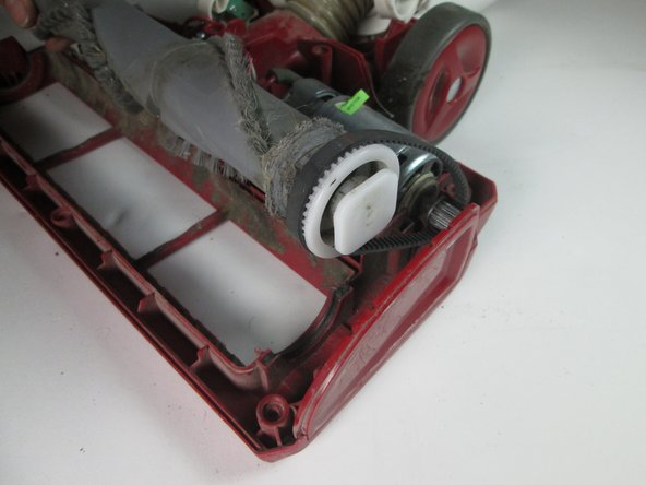 Remove the roller belt from around the roller brush and the motor gear.