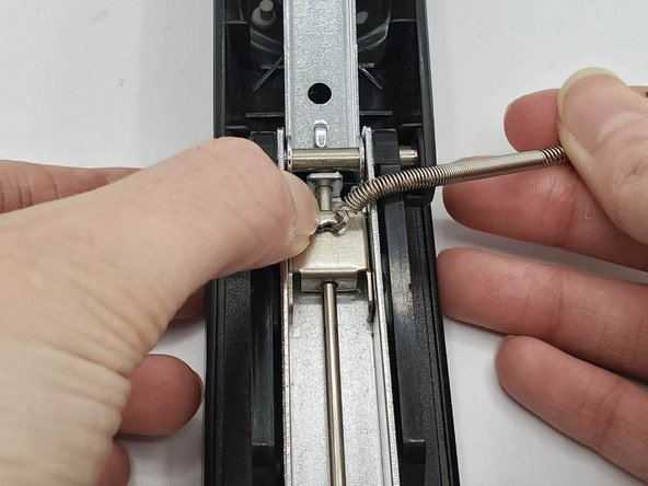 Clamp the pusher's hook closed using your thumb.