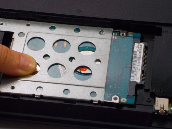 Slide the hard drive to the left, unlocking it from its default position.