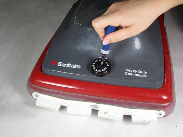 Stand the vacuum upright, unscrew the single screw located on the center dial using a Torx T20 screwdriver and remove the dial form the vacuum body.