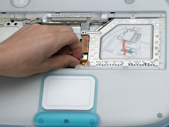 Loosen the trackpad clamp by pulling the top piece up slightly, freeing the trackpad ribbon.