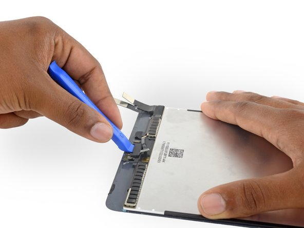 Use a plastic opening tool to pry the home button bracket off the display assembly.