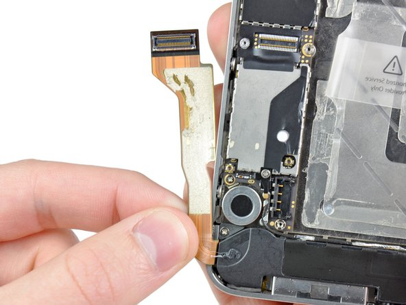 Peel the dock connector cable off the adhesive securing it to the logic board and the side of the speaker enclosure.