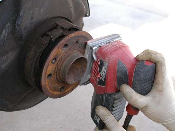 Use a fine grit sandpaper, and optionally a power sander, to work around the flat surface of the hub to remove rust.