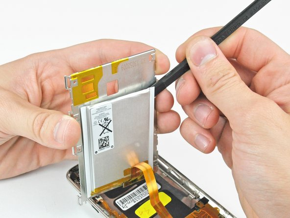 Use the flat end of a spudger to pry the battery off the adhesive securing it to the metal display tray.