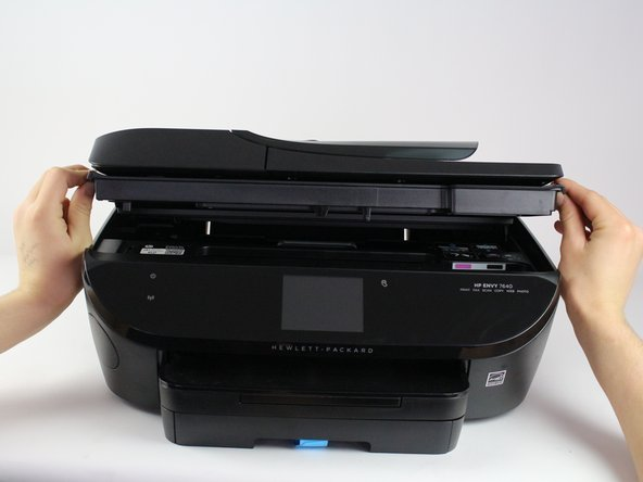 Open the printer by pushing upwards on the plastic tabs located on the sides of the printer.