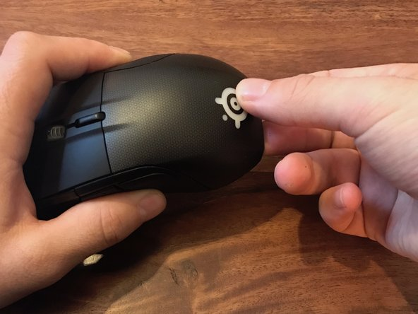 Use both your index and thumb to gently pry the top cover out from the mouse.