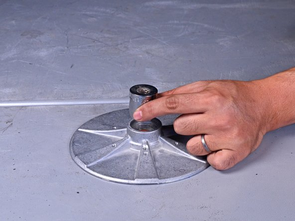 """Place a 15/16"""" socket inside the center of the sanding disc and use a mallet to tap the bearing out of the disc."""