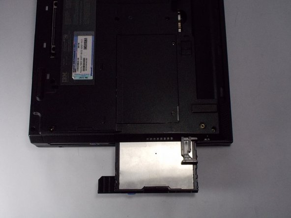 Pull the small black tab away from the computer to access the drive.