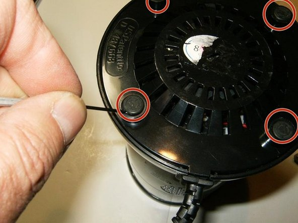 With the blade gear removed, it is time to focus on the power base. Use a small screwdriver or similar to remove the four rubber feet from the base. No glue is used, they are simply pressed in the openings