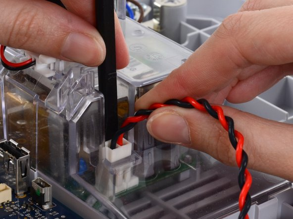 Grasp the power supply cable firmly and lift both it and the spudger from the channel in the power supply housing to unplug the connector.