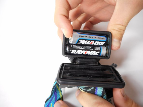 Remove the old batteries by pulling outward the positive end of each battery.