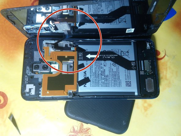 Once all the adhesive has separated, slowly rotate the back glass up and off the phone to the right, being careful of the ribbon cables still attached to the phone.