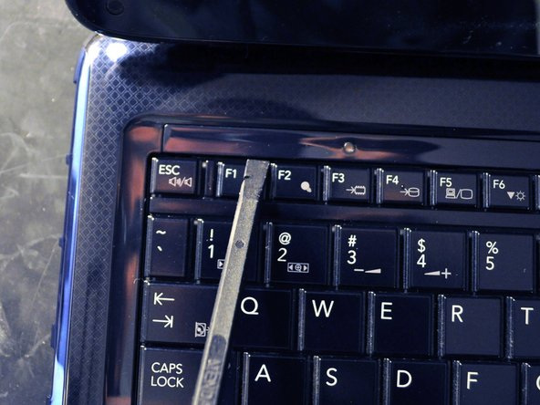 Use a spudger to carefully pry up the keyboard screw cover.