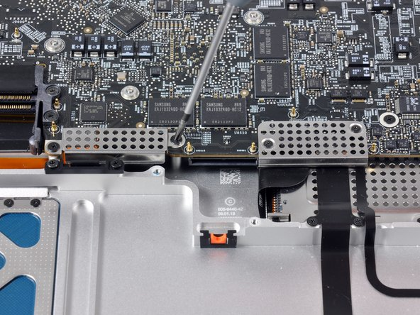 Removing the Phillips screws securing the  perforated metal covers to the Unibody. These covers seem to protect the ribbon cable connections for the trackpad, keyboard, express card, and the serial ATA hard drive.  Apple hasn't used metal shields like this before.