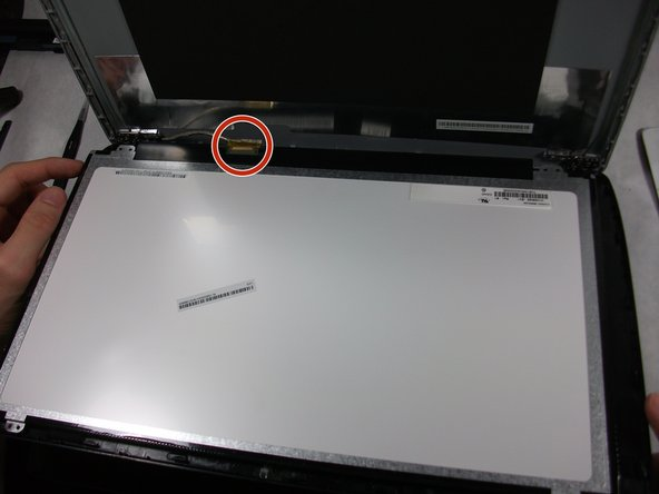 Peel up the tape over the connector and unplug the screen from the laptop.