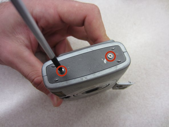 Remove two .085 inch Phillips screws from the left side of the camera using a #00 Philips screwdriver.