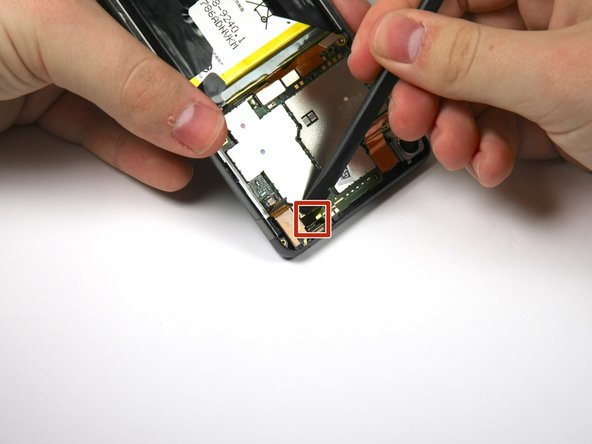 Use the spudger to loosen the black connector from the top right of the motherboard.