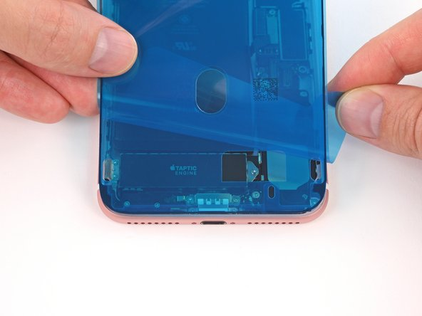 Before applying the adhesive, make sure your iPhone's battery connector lays flat so it doesn't press against the blue release liner. It's okay to temporarily reconnect the battery if needed—just be sure to disconnect it again before installing the display.