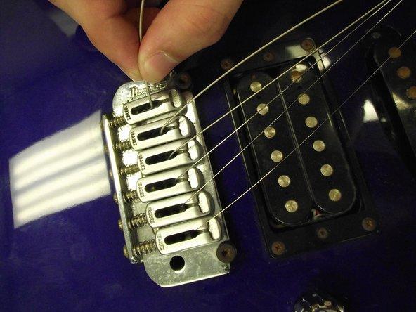 At the bridge, push each string through the guitar.