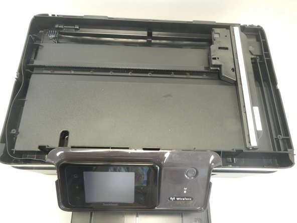 Gently pick up the scanner piece as shown to see the bottom side and wiring.