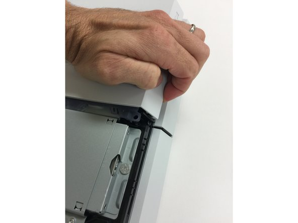 FIRST remove the two screws securing the top cover to the PS4. Removing the top cover will be easier if you follow these steps in order: