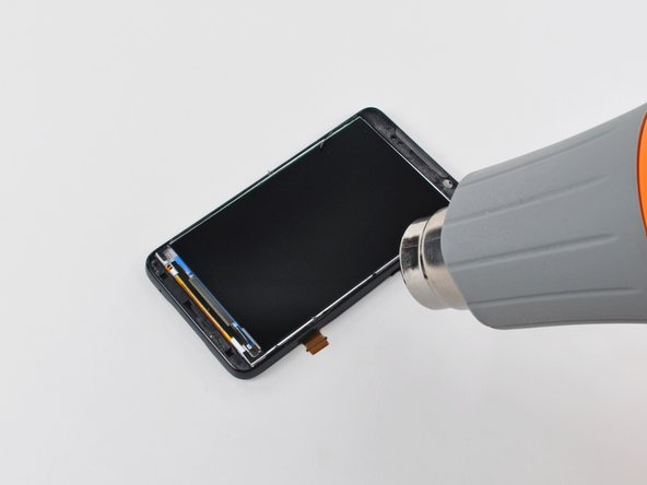 Use your heat gun to soften the adhesive under the LCD panel along its right edge.