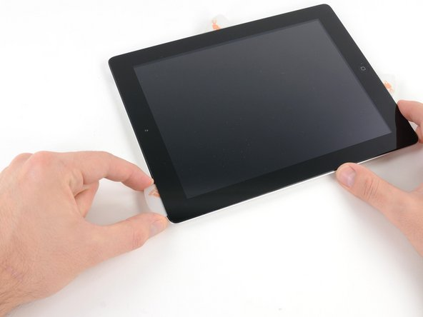 Continue releasing the adhesive along the top edge of the iPad, and slide the opening pick around the top left corner.