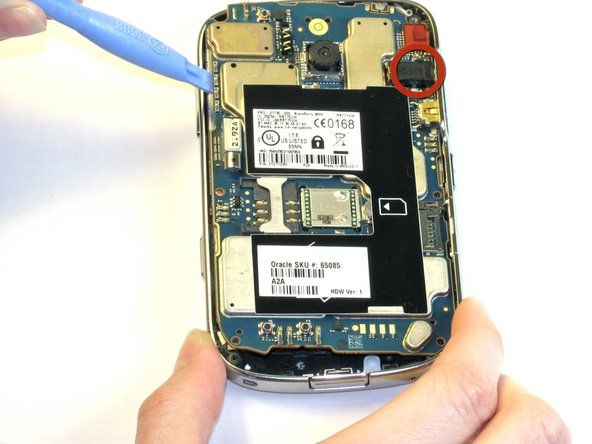 Using the same plastic opening tool, lift out the motherboard assembly.