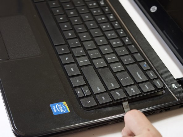 Starting from the left side, use the metal spudger to pry off the keyboard.