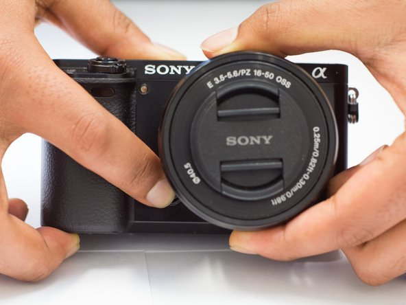 Use the finger, press and hold the release black circle button ( on the bottom ) next to the lens  on the front of the camera.