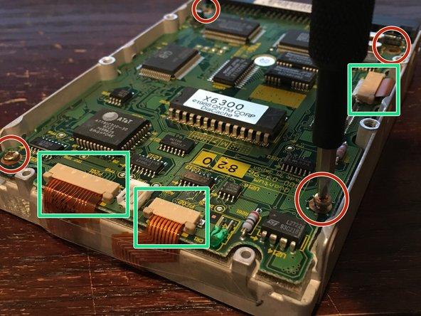 Remove the four Phillips PH1 screws (circled in red) holding the PCB onto the back of the drive.