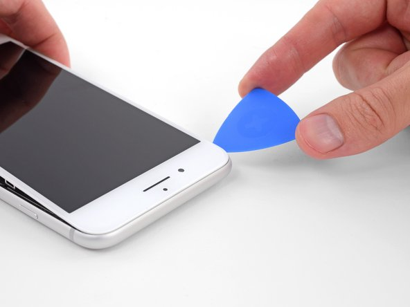 Slide an opening pick underneath the display along the top edge of the phone to loosen the last of the adhesive.