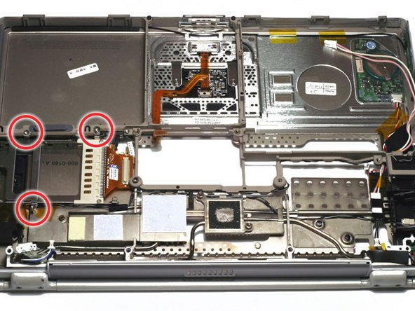 Remove the two T8 Torx screws that secure the PC Card cage.