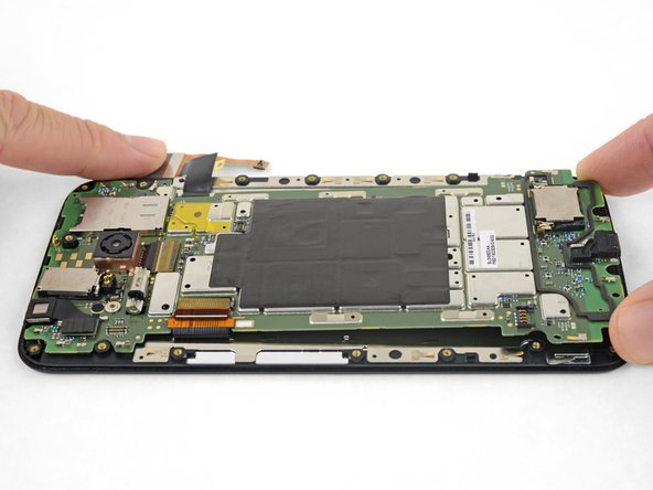 Starting at the bottom, lift the motherboard away from the display assembly.
