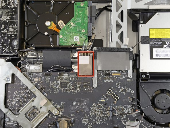 Locate the AirPort card at the top center of the logic board and just below the hard drive.