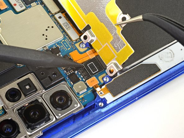 Use the pointed end of a spudger to disconnect the wireless charging coil connector from the motherboard.