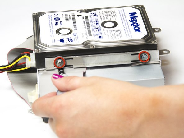 Using a Torx #10 screw driver, remove the four 6.03mm screws mounting the hard drive to the assembly.