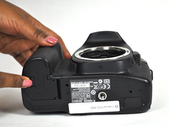 """Find the marked arrow on the battery compartment cover labeled """"BATT. OPEN"""". Slide the lever following the arrow's direction and lift at the same time to release the latch."""