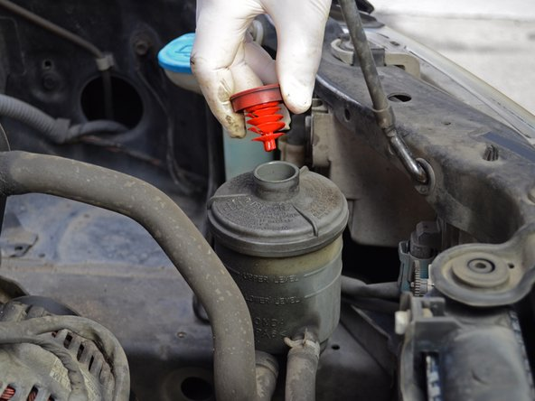 Locate the power steering reservoir near the front right corner of the engine bay.