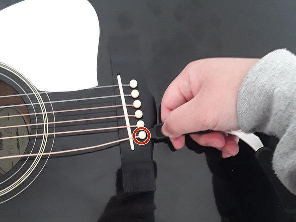 Use the pin remover in the All-In-1 Restringing Tool to remove the pin from the bridge