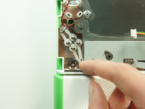 Push the four power button retaining clips through the bottom of the case with the tip of a screwdriver.