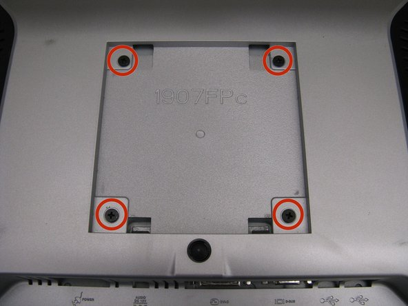 Carefully place the monitor face down on a flat surface, being careful to protect the display.